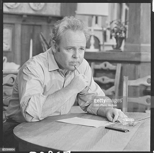 American actor Carroll O'Connor , as Archie Bunker, sits at a round table and thinks, a pencil to his chin, as he writes a letter in a scene from an...