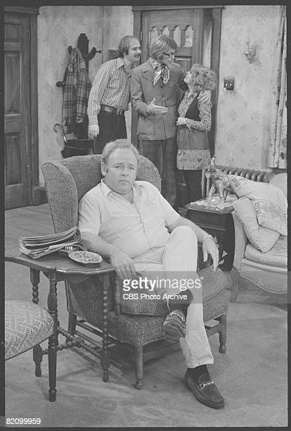 American actor Carroll O'Connor , as Archie Bunker, sits in an armchair in a scene from an episode of the television series 'All in the Family'...