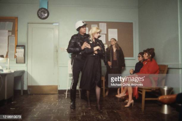 American actor Charles Shull plays a policeman apprehending American singer and musician Cherie Currie, of 'The Runaways', as American actress Jodie...