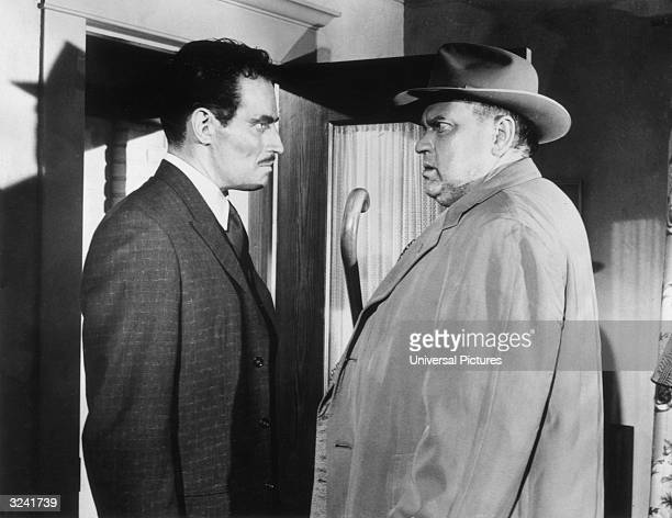 American actor Charlton Heston and American actor and film director Orson Welles speak to each other in a scene from Welles's film 'A Touch of Evil'