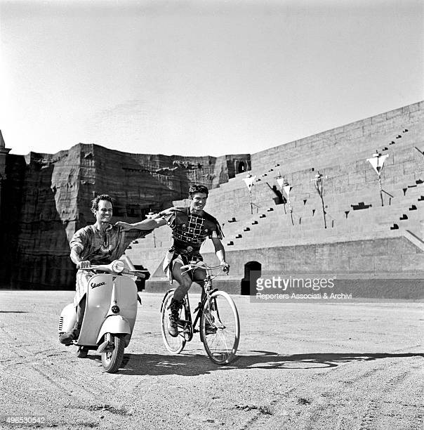 American actor Charlton Heston and British actor Stephen Boyd wearing stage costumes having fun in riding a Vespa and a bicycle on the set of the...