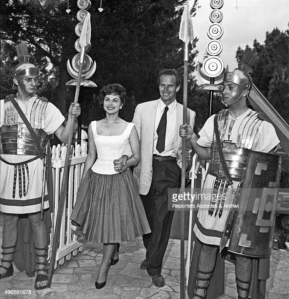 American actor Charlton Heston arriving arm in arm with his wife and American actress Lydia Clarke on the path leading to the cocktail in Cinecittà...