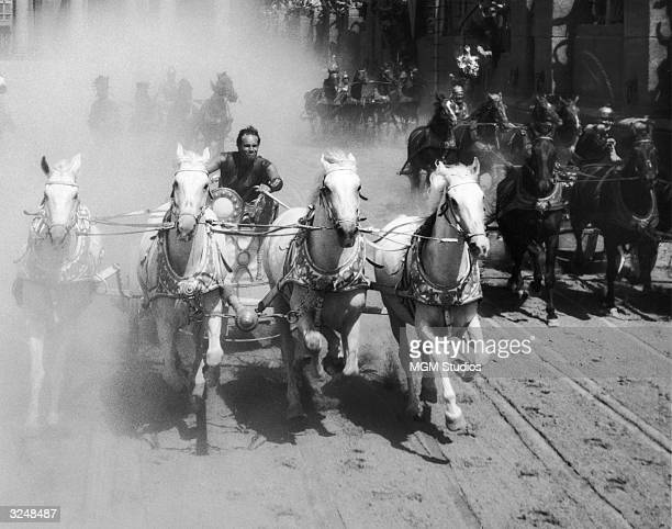 American actor Charlton Heston competes in a chariot race in a still from the film 'Ben Hur' directed by William Wyler