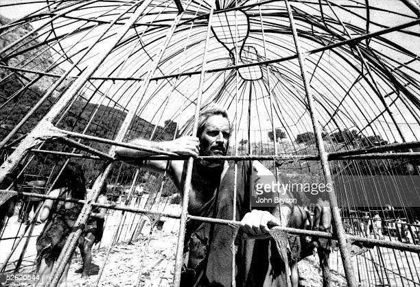 American actor Charlton Heston dressed in rags looks out from inside a makeshift cage in a scene from the film 'Planet of the Apes' directed by...