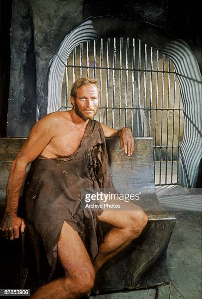 American actor Charlton Heston dressed in rags sits on a stone bench in jail in a still from the film 'Planet of the Apes' directed by Franklin J...