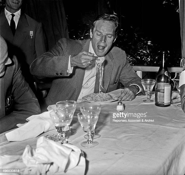 American actor Charlton Heston eating spaghetti in a restaurant Rome 1960
