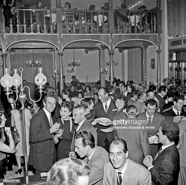 American actor Charlton Heston having a drink with American director William Wyler and Israeli actress Haya Harareet at the restaurant 'Vecchia...