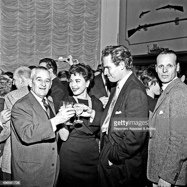American actor Charlton Heston having a toast with American director William Wyler and Israeli actress Haya Harareet at the restaurant 'Vecchia...