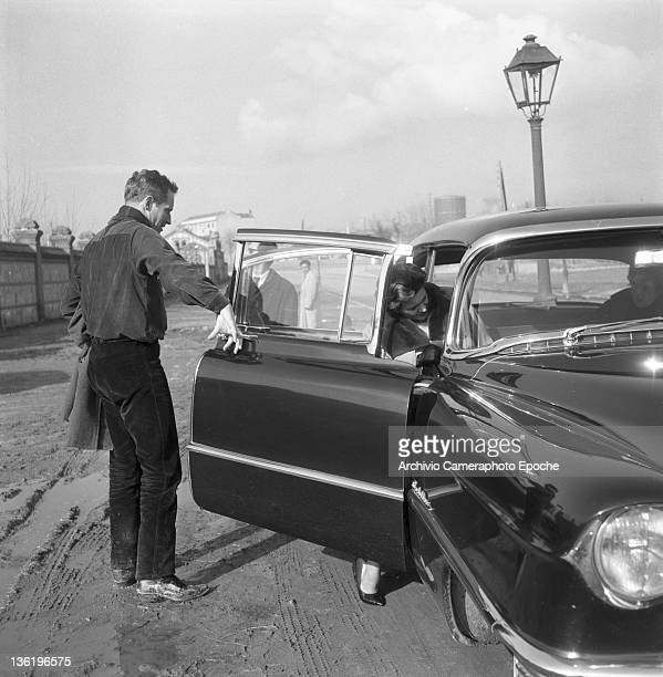 American actor Charlton Heston helping out his wife Lydia Clarke to get into a car Lido Venice 1961