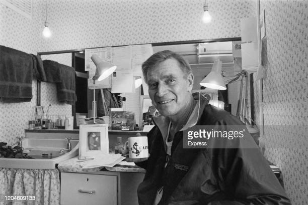 American actor Charlton Heston holding a mug with the legend 'USS Caine', in his dressing room at the Queen's Theatre, where he was directing a stage...