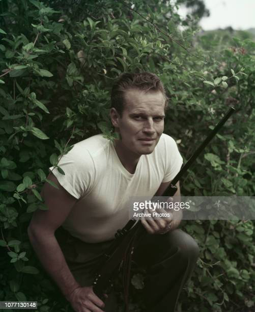 American actor Charlton Heston holding a rifle circa 1955