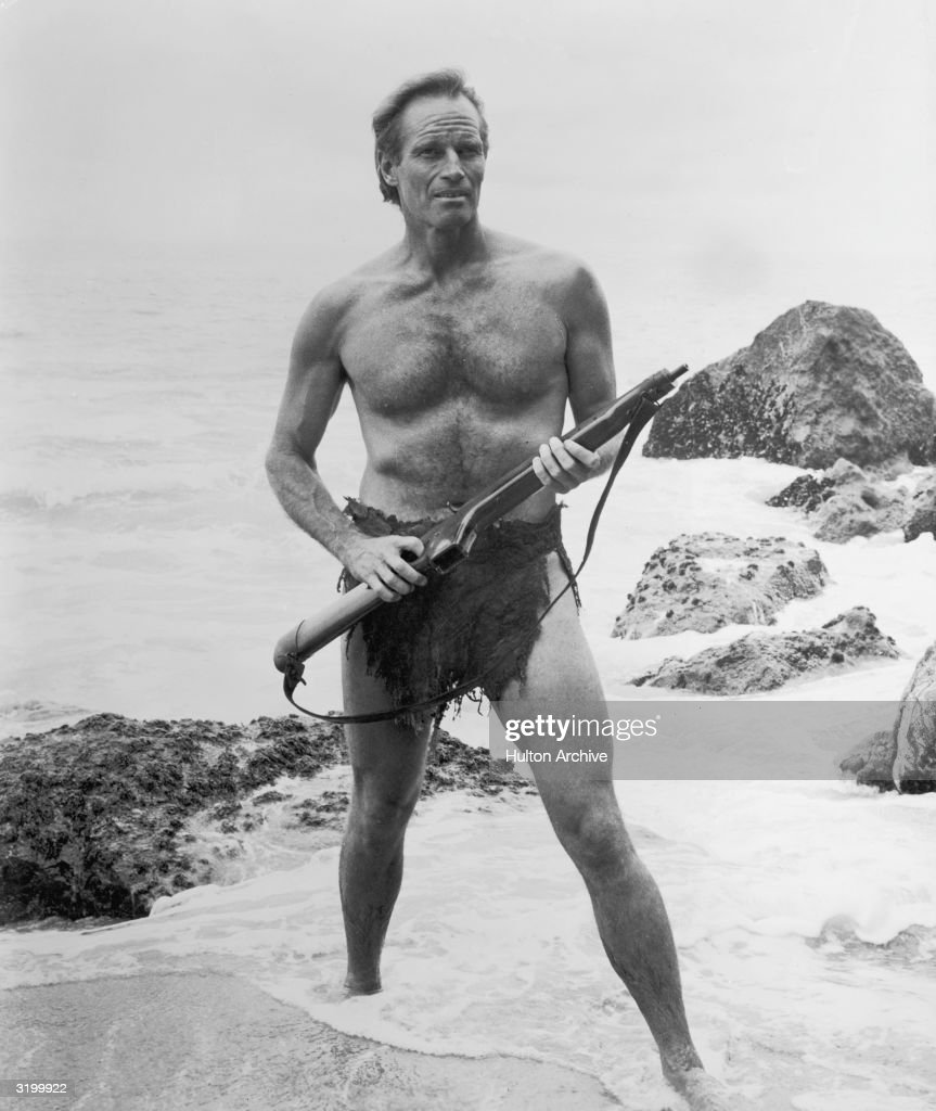 american-actor-charlton-heston-holds-a-rifle-as-he-stands-in-the-surf-picture-id3199922