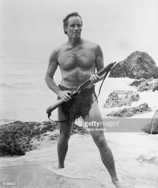 American actor Charlton Heston holds a rifle as he stands in the surf in a still from director Franklin Schaffner's film 'Planet of the Apes' He is...