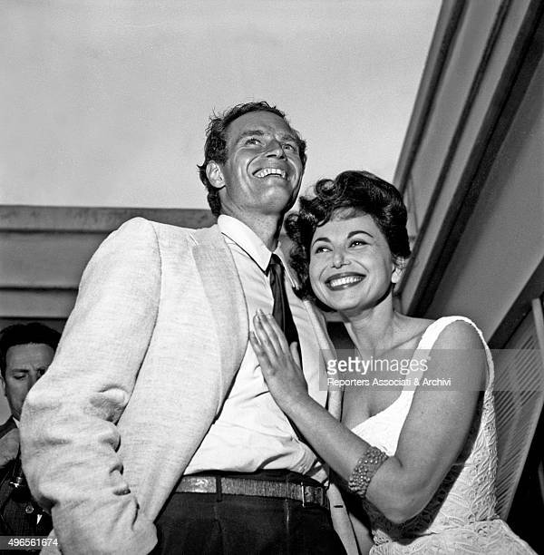 American actor Charlton Heston hugging his wife and American actress Lydia Clarke at the cocktail in Cinecittà for the inauguration of the shooting...