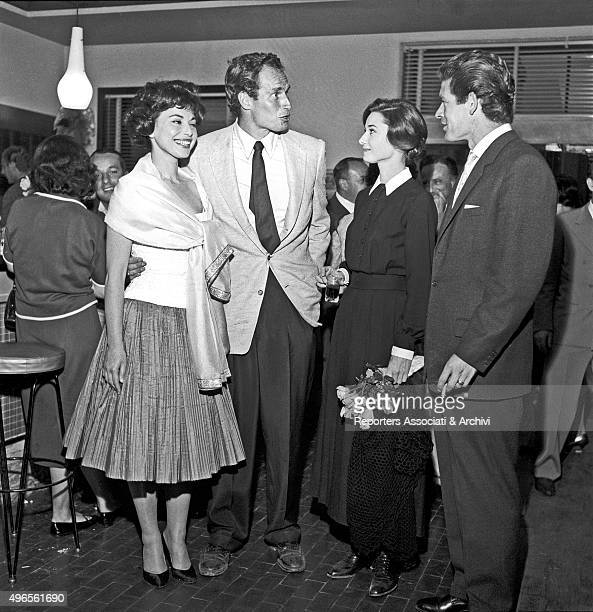 American actor Charlton Heston hugging his wife and American actress Lydia Clarke while talking to British actress Audrey Hepburn and British actor...