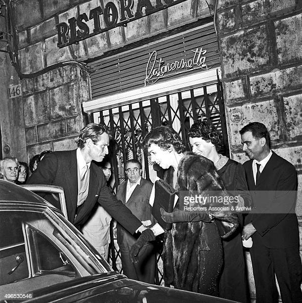 American actor Charlton Heston in Rome to shoot the film 'Ben Hur' leaving teatro Sistina and helping his mother Lila Charlton to get on board the...