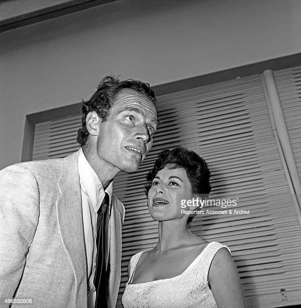 American actor Charlton Heston listening to his wife American actress Lydia Clarke during the cocktail party in the studios of Cinecittà before...