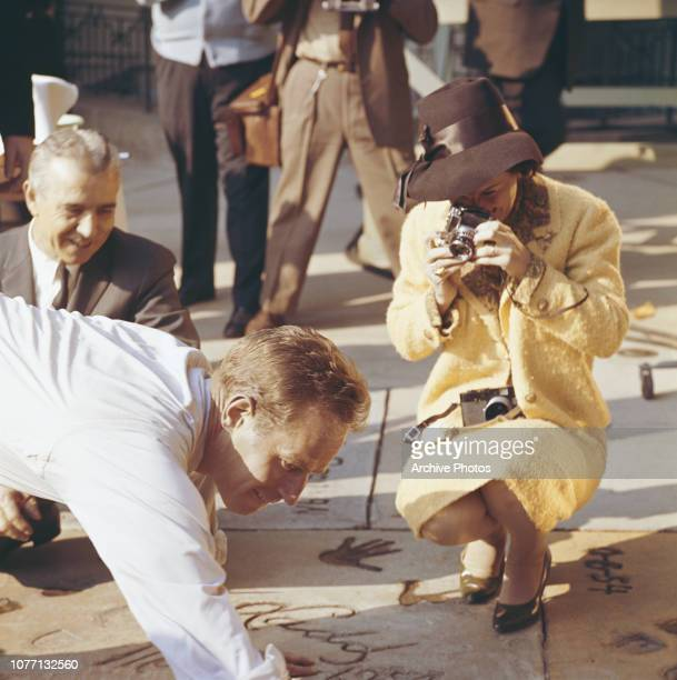 American actor Charlton Heston plants his handprints in cement outside Grauman's Chinese Theatre Hollywood California 18th January 1962 He is being...