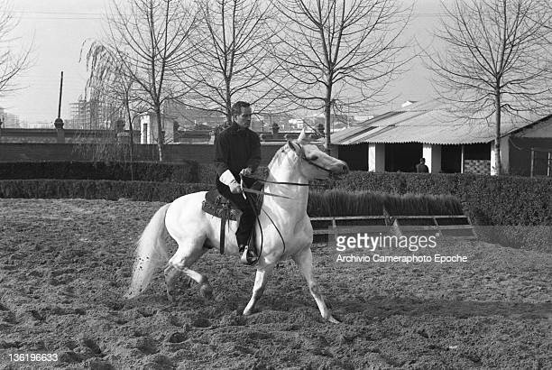 American actor Charlton Heston riding a horse in a paddock Lido Venice 1961