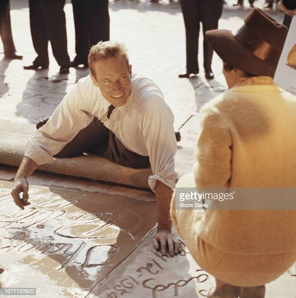 American actor Charlton Heston signs his name in cement under his handprints outside Grauman's Chinese Theatre Hollywood California 18th January 1962...