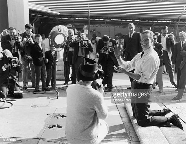 American actor Charlton Heston smiles for a crowd of fans and photographers as he holds up his cementcovered hands shortly after imprinting them...