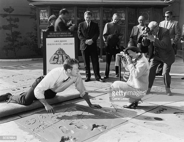 American actor Charlton Heston smiles for photographers as he signs his name on his square along the Hollywood Walk of Fame, Grauman's Chinese...