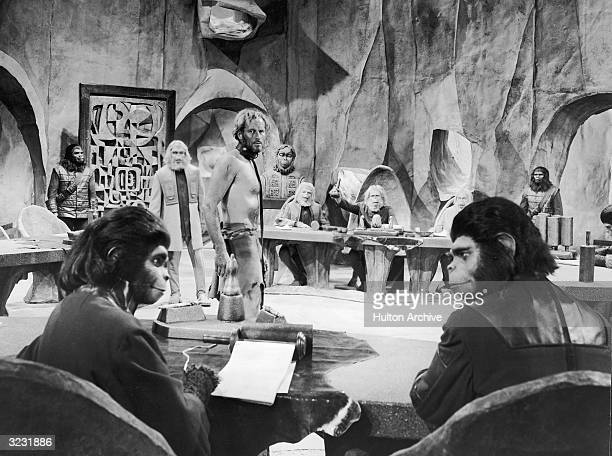 American actor Charlton Heston stands before the judicial council of Orangutans while American actor Kim Hunter as Dr Zira and British actor Roddy...