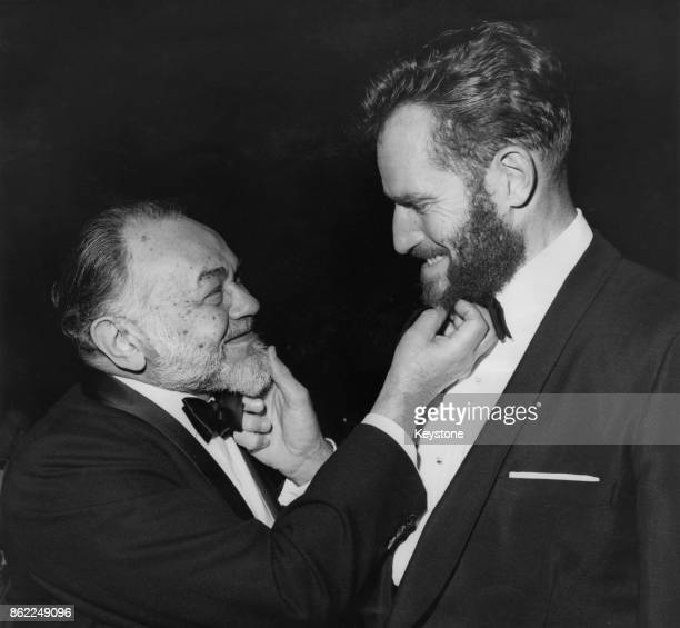 American actor Charlton Heston tugs the beard of fellow actor Edward G Robinson at the annual awards dinner of the Directors' Guild at the Beverly...