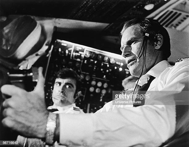 American actor Charlton Heston with football playerturned actor Mike Henry as his copilot in a scene from the film 'Skyjacked' 1972
