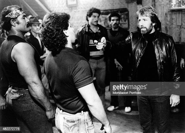 American actor Chuck Norris aiming the gun at a man in the film Code of Silence 1985