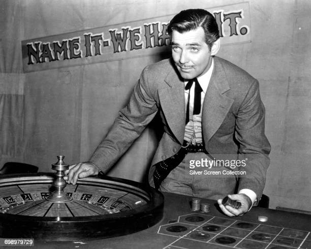 American actor Clark Gable as con man Candy Johnson in the western 'Honky Tonk', 1941. A sign behind him reads 'Name it - We Have it'.
