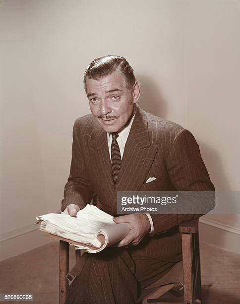 American actor Clark Gable reading a script circa 1955