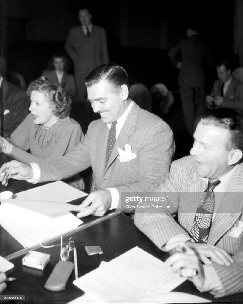 American actor Clark Gable (1901 - 1960) (center) shares a laugh with unidentified cast mates during a script read-through, mid 1950s.