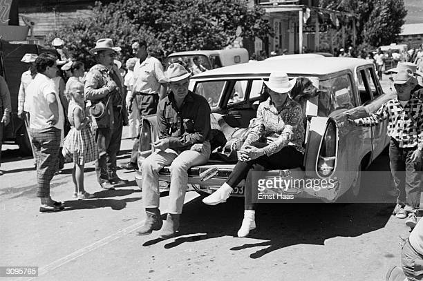 American actor Clark Gable sits on the boot of a car on the set of John Huston's 'The Misfits' filming on location in the Nevada Desert