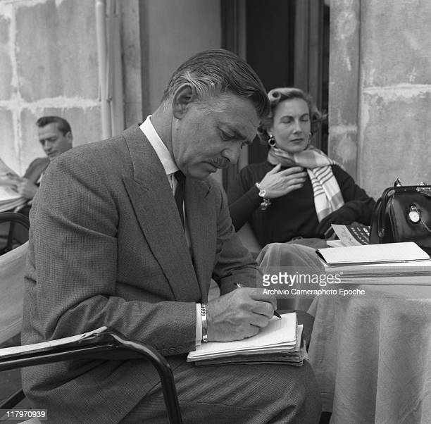American actor Clark Gable sitting at a bar table outdoor writing with a pen on a notepad his bridetobe Kay Williams Spreckles sitting behind her...
