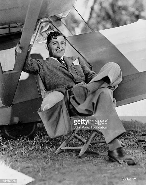 American actor Clark Gable sitting beside an aircraft during the filming of 'Too Hot To Handle' in which he plays a news reporter covering the...