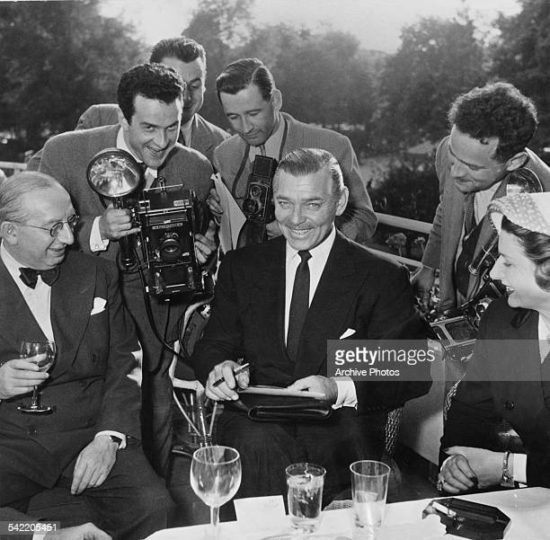 American actor Clark Gable surrounded by photographers circa 1955 One is holding a Speed Graphic camera