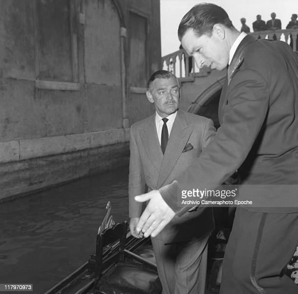 American actor Clark Gable wearing a suit and a tie getting on a gondola invited by a hotel usher Venice 1953