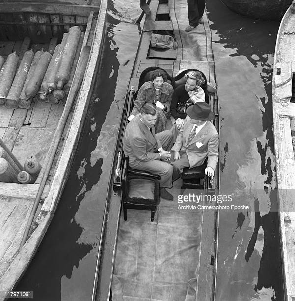 American actor Clark Gable wearing a suit and a tie sitting on a gondola with his bridetobe Kay Williams Spreckles and another couple portrayed from...