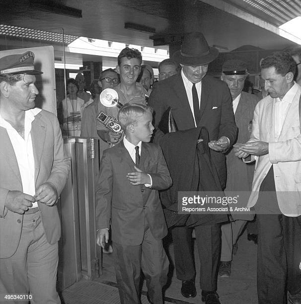 American actor Clark Gable with his stepson Adolph Spreckels surrounded by onlookers and a photograph while arriving at Termini railway station Rome