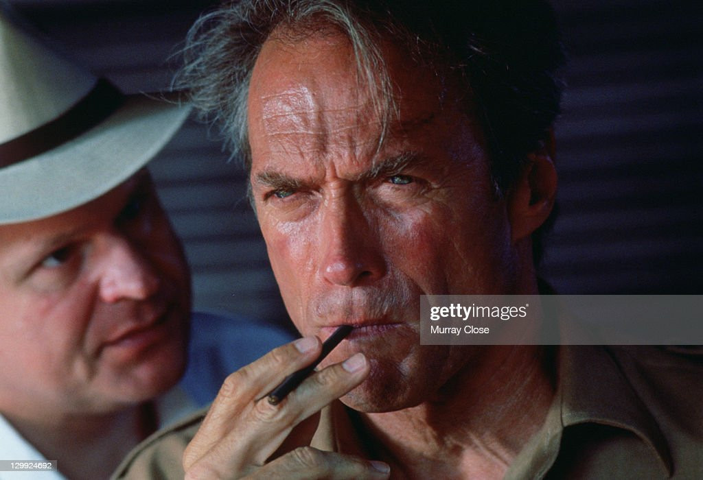 American actor Clint Eastwood as filmmaker John Wilson and George Dzundza as Paul Landers in a scene from the film 'White Hunter Black Heart', 1990. Eastwood is smoking a cheroot.