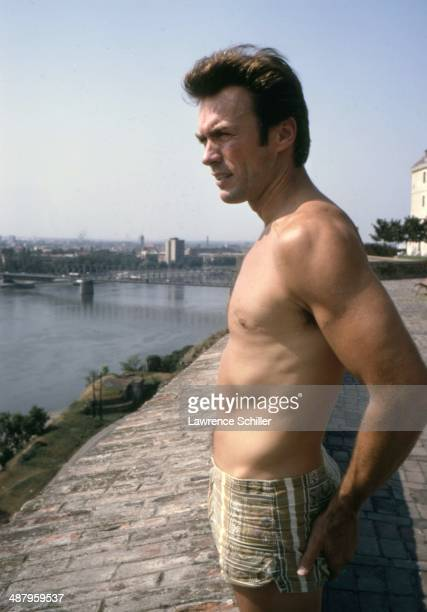 American actor Clint Eastwood dressed in a swimsuit looks down over an unidentified river Vizinada Yugoslavia 1969