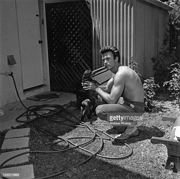 American actor Clint Eastwood with a pet dog and cat at his home in the Hollywood Hills Los Angeles California circa 1960
