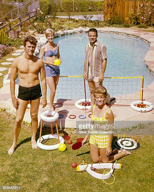 American actor Clint Eastwood with his wife, Maggie , and friends by a swimming pool, circa 1960.