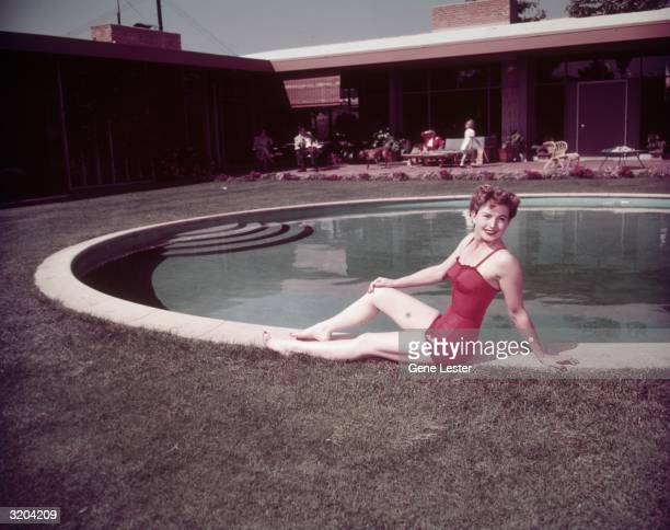 American actor Coleen Gray wearing a red swimsuit poses at the edge of a paddock pool outdoors at the home of interior decorator Paul Lazslo...