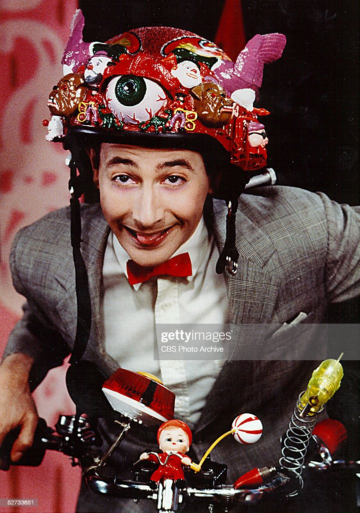 American actor, comedian, and children's show host Paul Reubens (as Pee Wee Herman) poses on his beloved bike in a television still from the CBS Television show 'Pee Wee's Playhouse', 1986.