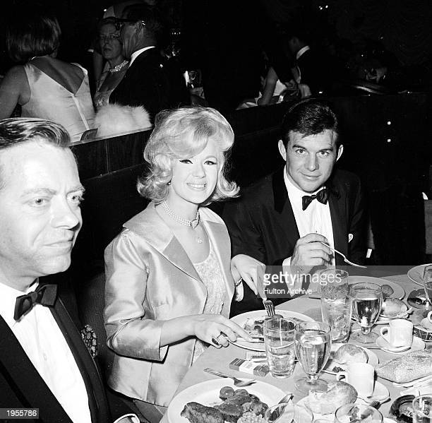 American actor Connie Stevens her husband James Stacy and American actpr Max Showalter eat during the Academy Awards ceremonies Santa Monica...