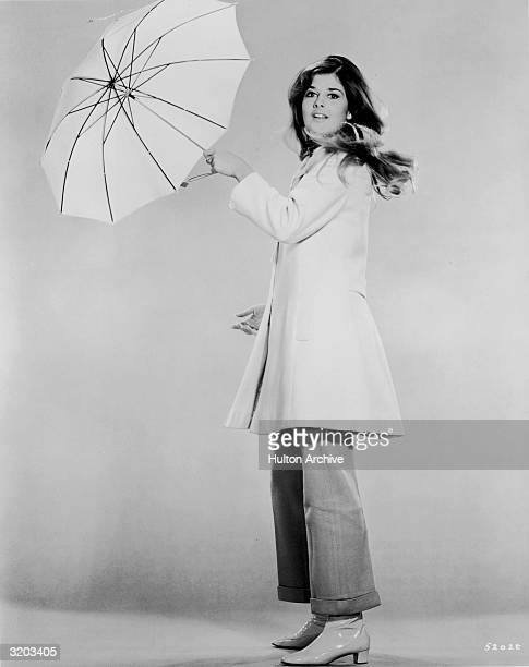American actor Cristina Ferrare swings an umbrella in a fulllength promotional portrait for director Michael Gordon's film 'The Impossible Years'...