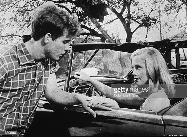 American actor Cybill Shepherd touches American actor Timothy Bottoms's hand while sitting in a convertible in a still from the film 'The Last...