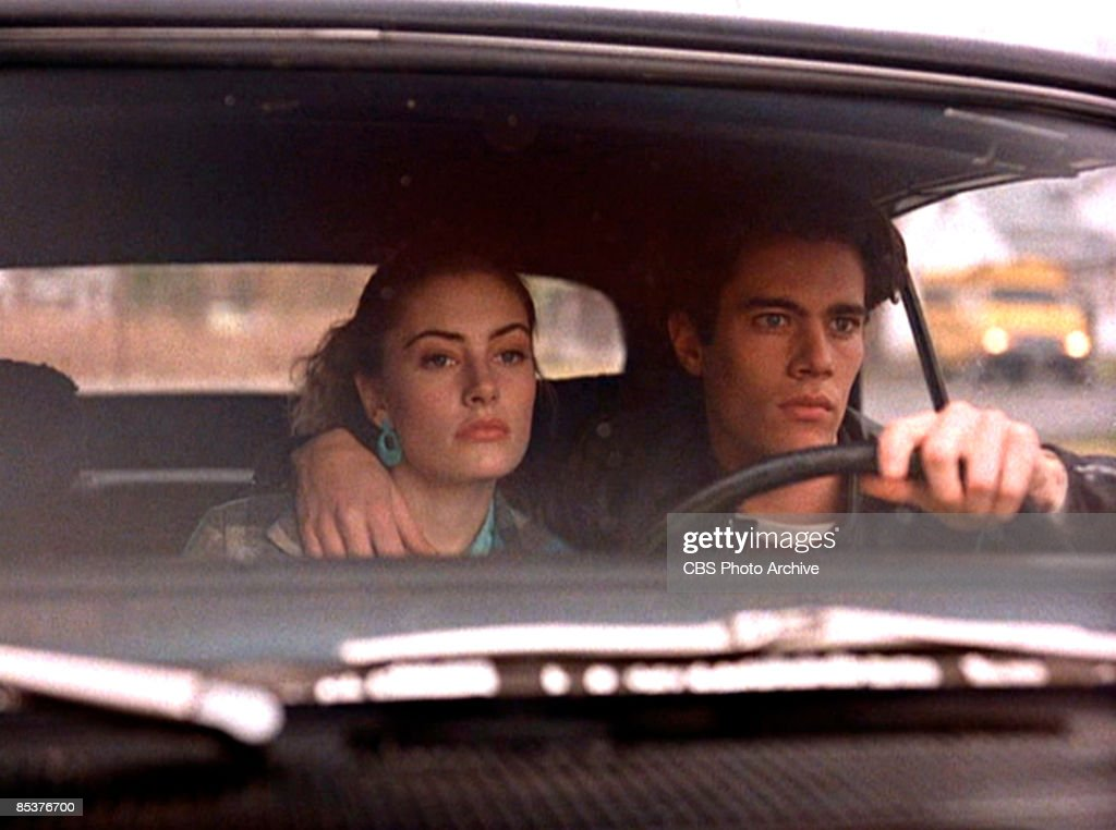 American actor Dana Ashbrook (as Bobby Briggs) (right) steers a car from behind the steering wheel with his other arm around the shoulders of actress Madchen Amick (as Shelly Johnson) in a scene from the pilot episode of the television series 'Twin Peaks,' originally broadcast on April 8, 1990.